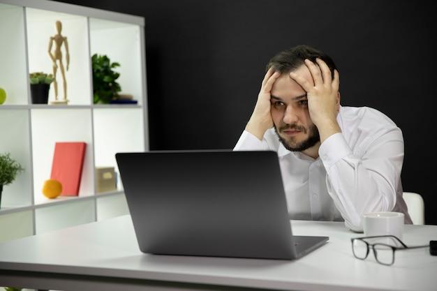 Depressed handsome freelancer sitting at desk in front of laptop in home office