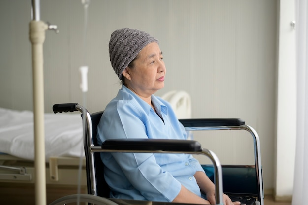 A depressed and hopeless asian cancer patient woman wearing head scarf in hospital.