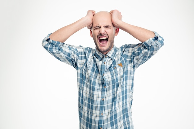 Depressed hysterical young man in checkered shirt screaming loudly over white wall