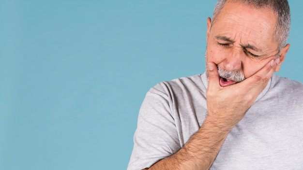 Depressed ill man having toothache and touching his cheek on blue backdrop
