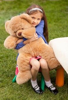 마당에 의자에 앉아있는 동안 큰 테디 베어를 안고 우울 어린 소녀