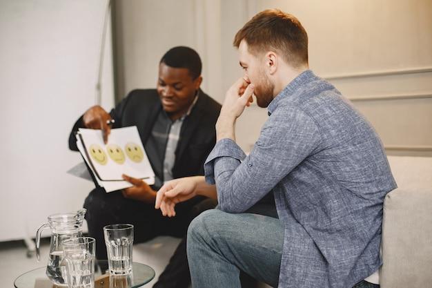 Подавленный человек на псикотерапии. консультант проводит тест, показывая фотографии своему пациенту-мужчине.