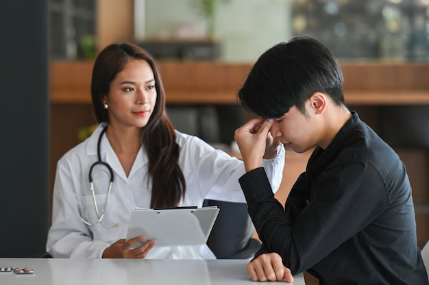 Depressed man consulting his health problem with female professional psychiatrist doctor.