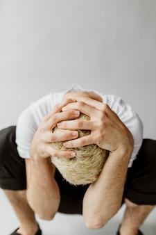 우울한 남자는 손으로 머리를 가린다
