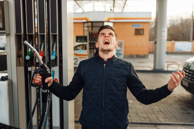 Depressed man cries on gas station, fuel filling