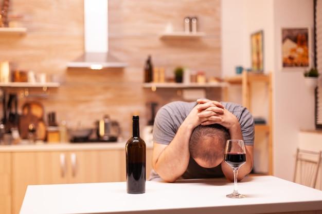 台所でのアルコール乱用の後に頭痛を持っているうつ病の男性。アルコール依存症の問題で疲れ果てた不幸な人の病気と不安感。