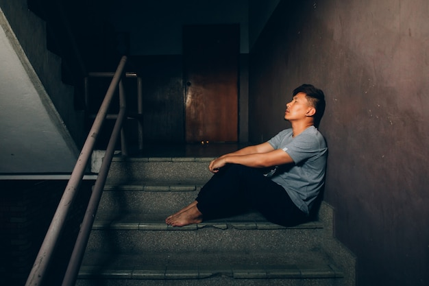 Depressed man.sad man sitting on the stairs in building