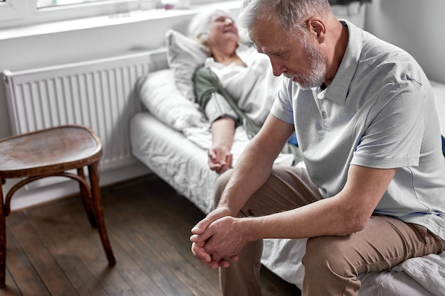Подавленный мужчина сидит рядом со своей больной пожилой женой, лежащей на кровати, страдая от болезни. в больнице