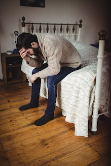 Depressed man sitting on bed