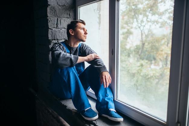 어두운 방에서 창틀에 앉아 우울한 남자, 사이코 환자. 정신병 사람들 개념, 스트레스 인간, 우울증
