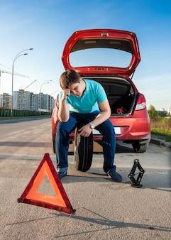 Depressed man sitting on spare wheel near broken car