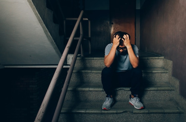 Depressed man sitting on the stairs in building and holding his forehead while having headache.