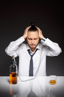 Depressed man sitting with a bottle of whiskey
