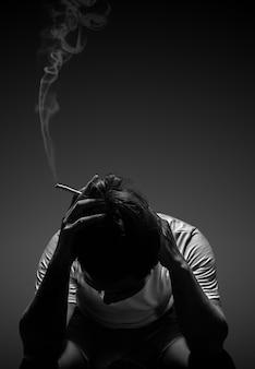 Depressed man smoking cigarette sitting on chair on black