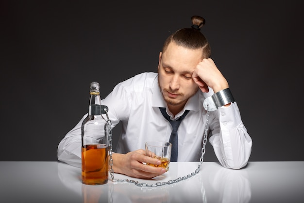 Depressed man spending time with a bottle of whiskey
