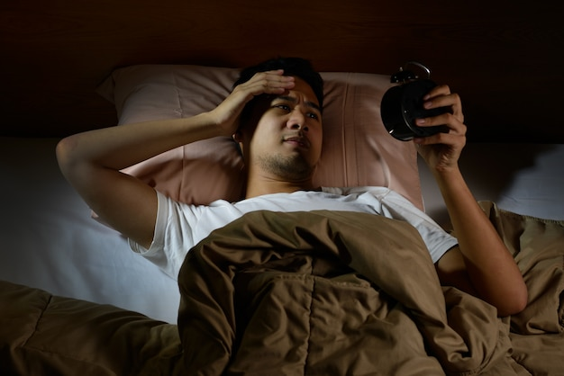 Depressed man suffering from insomnia looking at alarm clock lying in bed