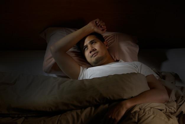 Подавленный человек, страдающий от бессонницы, лежа в постели