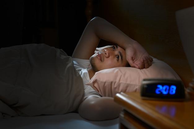 ベッドで横になっている不眠症に苦しんで落ち込んでいる男