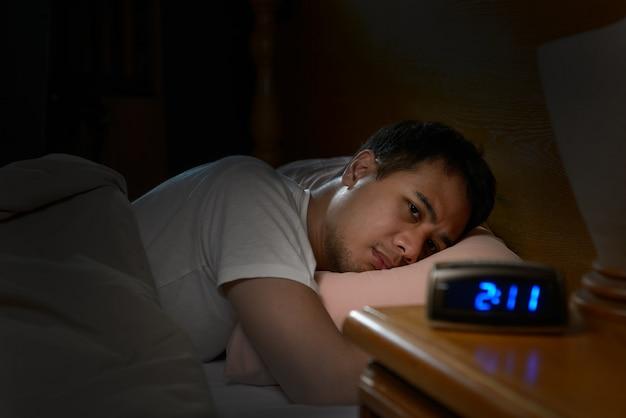 불면증으로 고통받는 우울한 남자가 침대에 누워