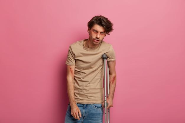 松葉杖で落ち込んでいる男性は、ドライバーの過失のために苦しんでいます