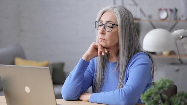 Подавленная зрелая женщина получила плохие онлайн-новости. синдром выгорания, переутомление, депрессия.