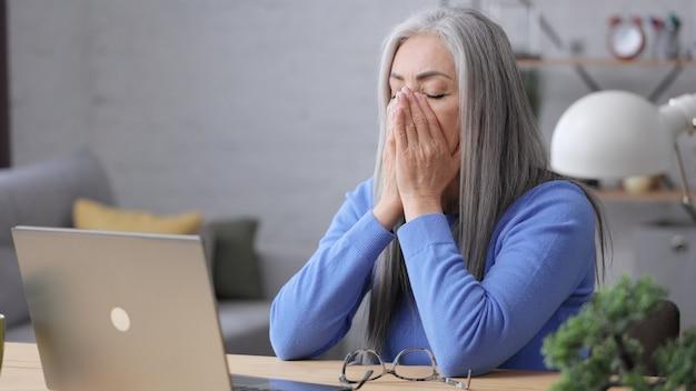 落ち込んでいる成熟した女性は悪いオンラインニュースを受け取りました。燃え尽き症候群、過労、うつ病。