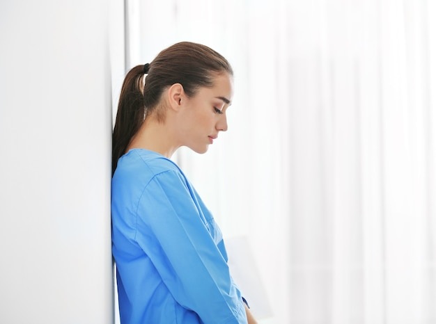 オフィスの壁の近くに立っている落ち込んでいる医療従事者