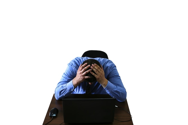 白い背景で隔離の落ち込んでいるサラリーマン。仕事のストレスの燃え尽き症候群。ひどい生活状況。机の上のラップトップの近くの男。