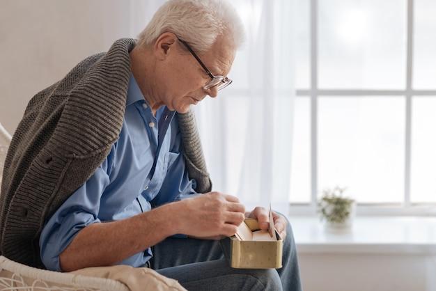 Подавленный пессимистичный пожилой мужчина сидит на кровати и переворачивает старое письмо, испытывая ностальгические чувства