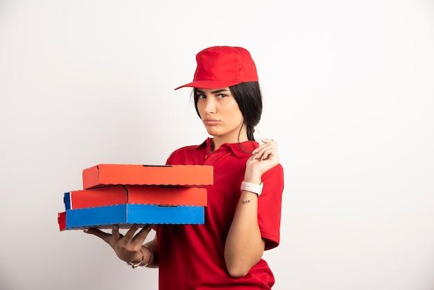 Donna depressa di consegna della pizza che tiene le scatole della pizza.