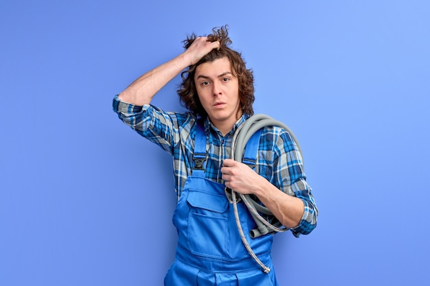 Depressed plumber with hose looking at camera holding hand on head upset