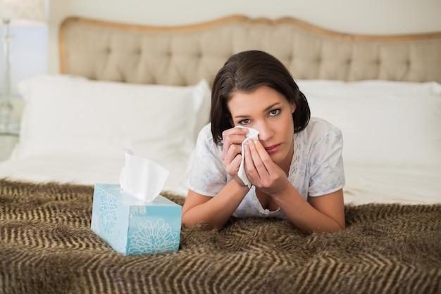 Депрессия довольно коричневоволосая женщина, вытирая глаза с ткани