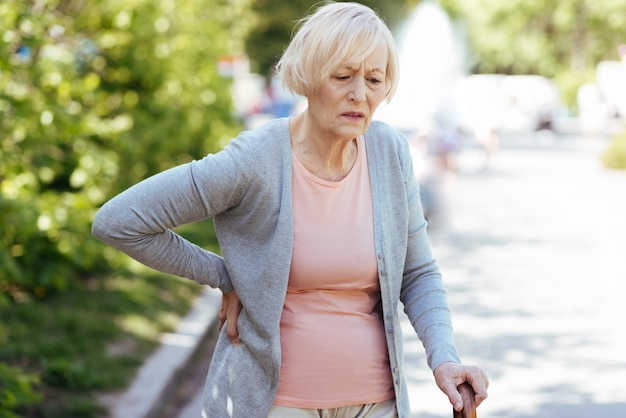 Depressed retired aged woman touching her back and leaning on the stick while suffering from backache outdoors