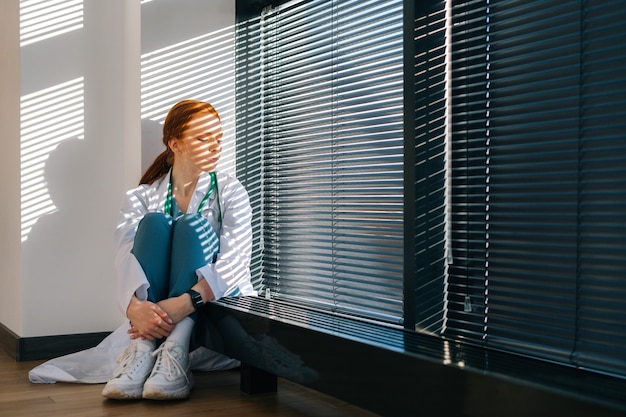 하얀 코트를 입은 우울한 여성 의사는 창 근처 바닥에 앉아 있는 머리 주위에 팔을 감습니다. 스트레스를 받은 화가 난 젊은 여성 의사는 전문적인 의료 과실에 대해 걱정하고 있습니다.