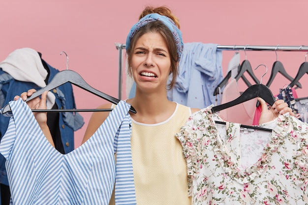 Depressed sad female standing at wardrobe holding two hangers with pieces of clothing feeling stressed