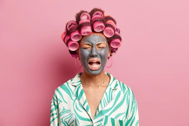 落ち込んだ悲しい女性が大声で悲しげな表情で顔の毛髪に美容マスクを付けるローラーはデートの準備をし、ピンクの壁にカジュアルな服装をした夫と別れを告げる