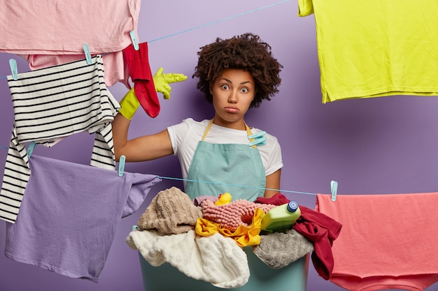 Depressed sad woman makes suicide gesture, has much work around house, dressed in casual apron, does washing during weekend, hangs clean clothes, poses indoor.