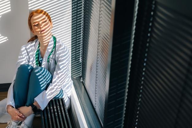 창가에서 손으로 다리를 껴안고 바닥에 앉아 있는 흰색 코트를 입은 우울한 젊은 여성 의사