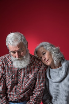 Depressed senior couple against colored background