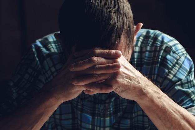 Подавленный старший закрывает лицо руками. болезнь альцгеймера