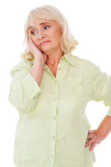 Depressed senior woman. depressed senior woman leaning her face on hand and looking away while standing isolated on white background