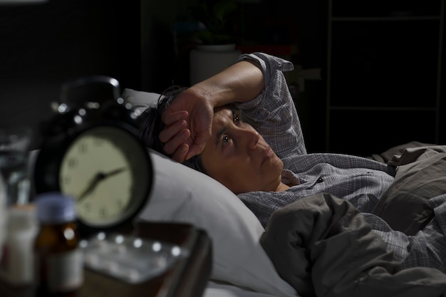 Depressed senior woman lying in bed cannot sleep from insomnia