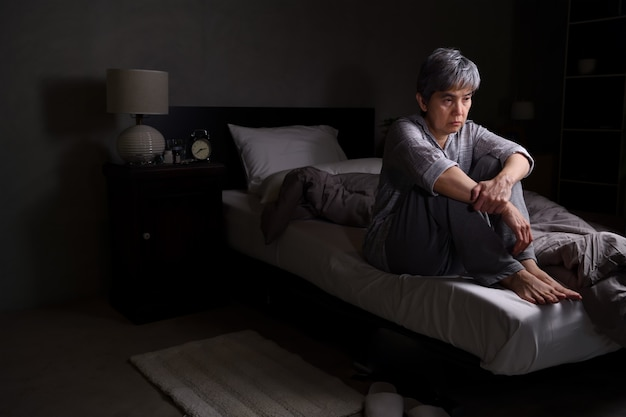 Depressed senior woman sitting in bed cannot sleep from insomnia