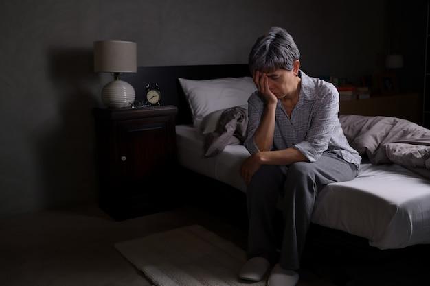 Подавленная старшая женщина, сидящая в постели, не может спать от бессонницы