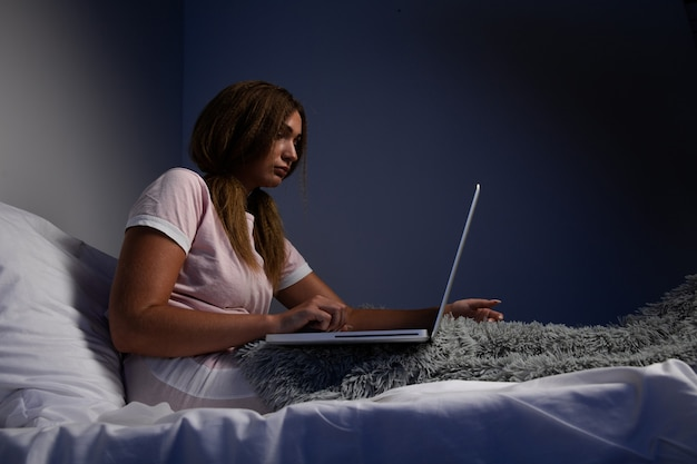 Depressed serious woman sitting in he bed and working on the laptop.