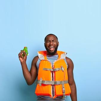 우울한 슬픔에 잠긴 흑인 남자는 느슨한 물 전투 게임에 불만을 느낍니다.