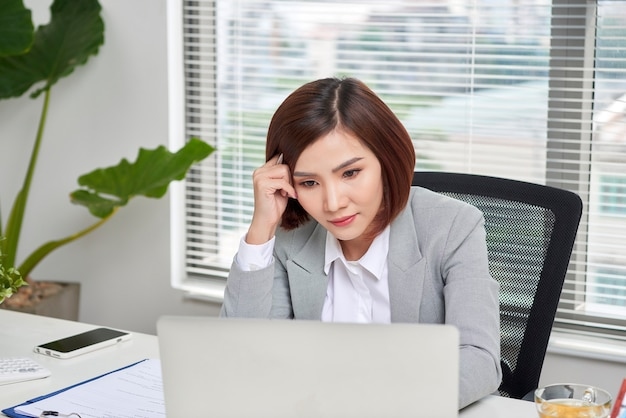 Depressed stressed young asian business woman with laptop suffering from trouble