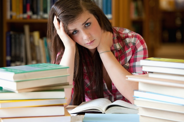 Depressed student surrounded by books