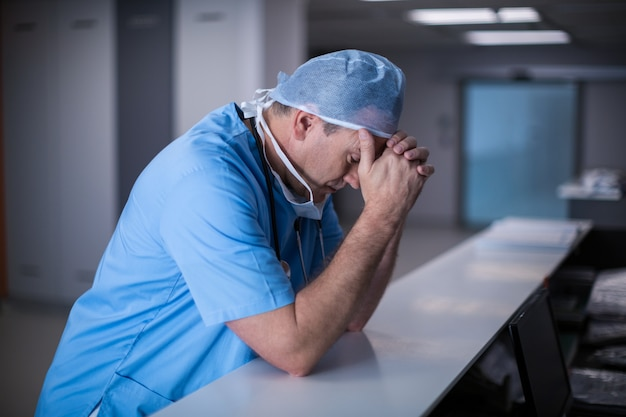 Depressed surgeon leaning on desk