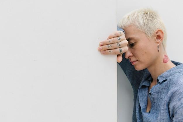 우울한 문신을 한 여자가 벽에 기대어 쉬고 있다
